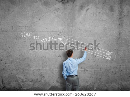 Rear view of businessman drawing sketches on wall - stock photo