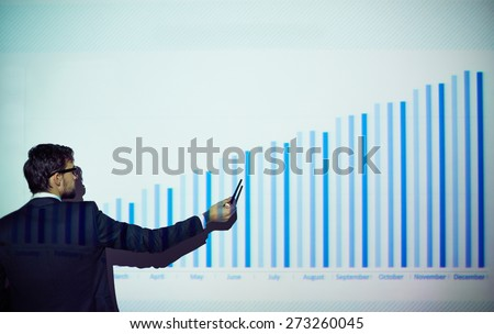 Rear view of businessman explaining chart on the wall