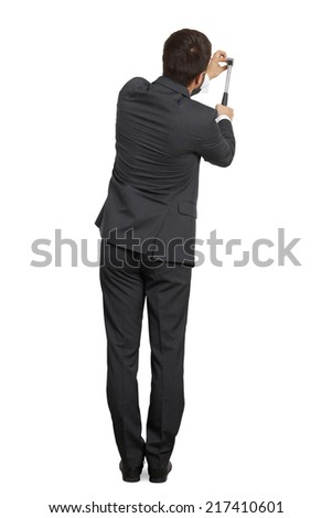 rear view of businessman hitting nail in the wall. isolated on white background