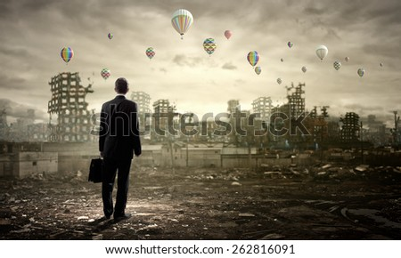 Rear view of businessman looking at aerostats flying above city - stock photo