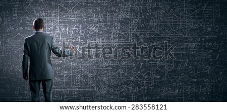 Rear view of businessman looking at business sketch on wall - stock photo