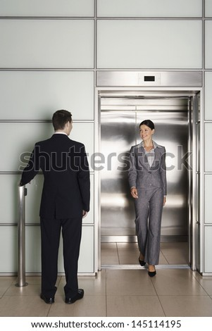 Rear view of businessman looking at female colleague exiting elevator in office - stock photo
