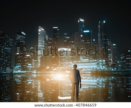Rear view of businessman looking at nighttime Singapore cityscape - stock photo