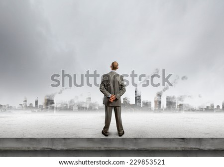 rear view of businessman looking at scene of polluted city