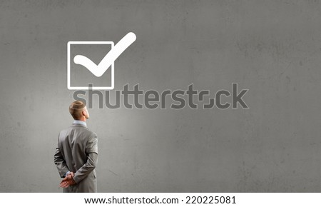 Rear view of businessman looking at tick above head - stock photo