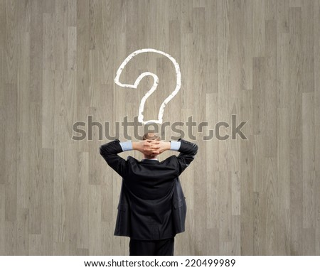 Rear view of businessman looking thoughtfully at question mark above head - stock photo