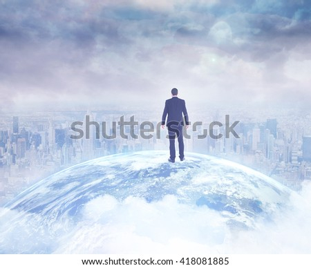 Rear view of businessman standing on a picture of the earth in a city - stock photo