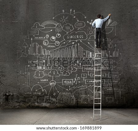 Rear view of businessman standing on ladder and drawing business sketch on wall - stock photo