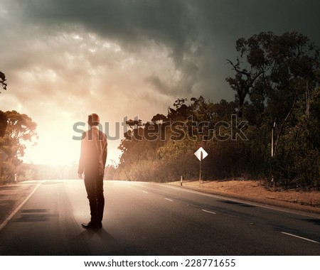 Rear view of businessman standing on road - stock photo
