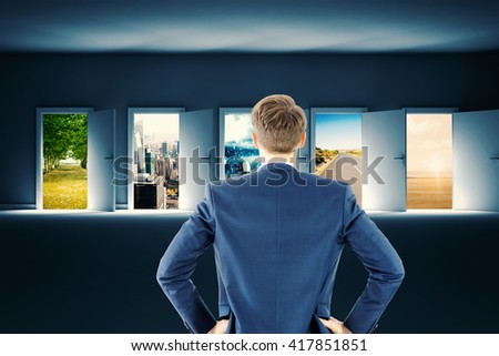 Rear view of businessman standing with hands on wiast against picture of a street - stock photo