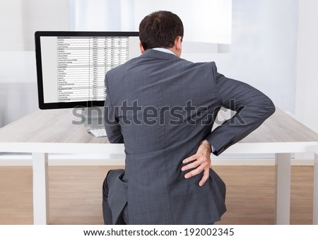 Rear view of businessman suffering from backache while sitting at computer desk in office