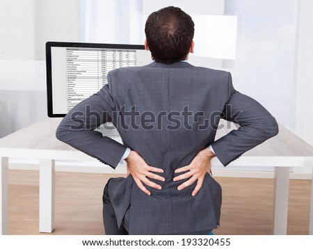 Rear view of businessman suffering from backache while sitting at computer desk in office - stock photo