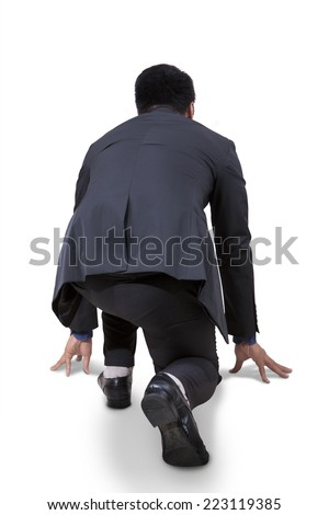 Rear view of businessman take a ready position to race and compete - stock photo
