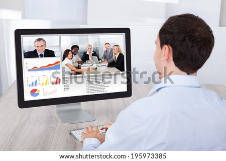 Rear view of businessman video conferencing with colleagues on desktop PC at office desk - stock photo