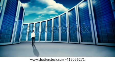 Rear view of businessman with hands in pockets against composite image of server towers - stock photo