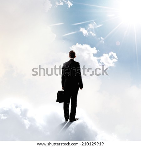 Rear view of businessman with suitcase standing on cloud - stock photo