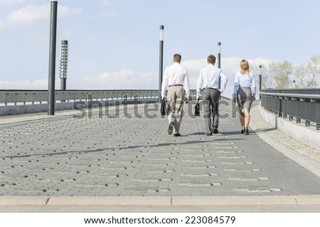 Rear view of businesspeople walking on bridge - stock photo