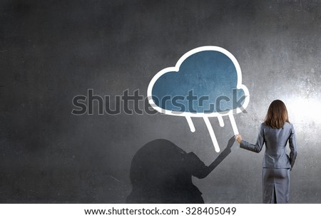 Rear view of businesswoman drawing cloud concept on wall