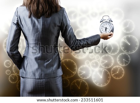 Rear view of businesswoman holding alarm clock in hand - stock photo