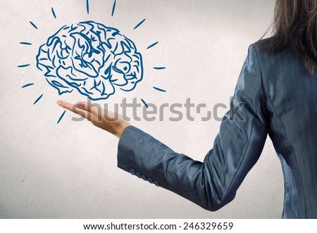 Rear view of businesswoman holding brain on palm - stock photo
