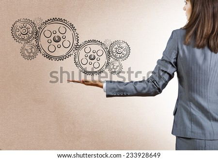 Rear view of businesswoman holding gears in palm - stock photo