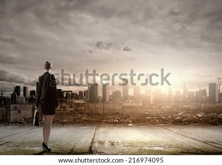Rear view of businesswoman looking at ruins of city - stock photo