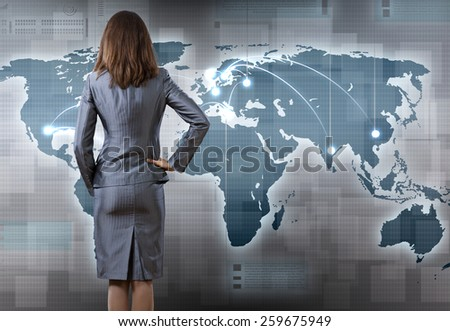 Rear view of businesswoman pointing at world map - stock photo