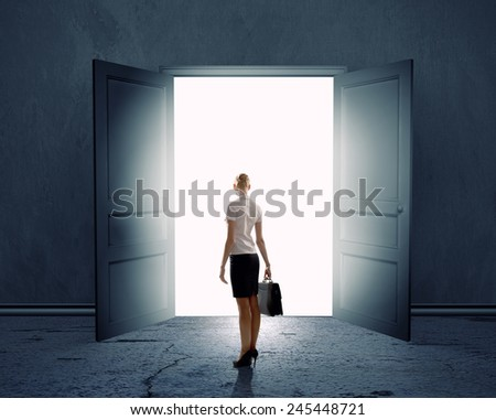 Rear view of businesswoman standing in light of opened door - stock photo