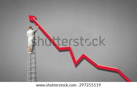 Rear view of businesswoman standing on ladder and reaching increasing graph