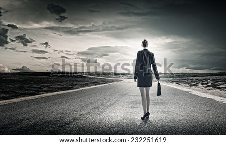 Rear view of businesswoman standing on road