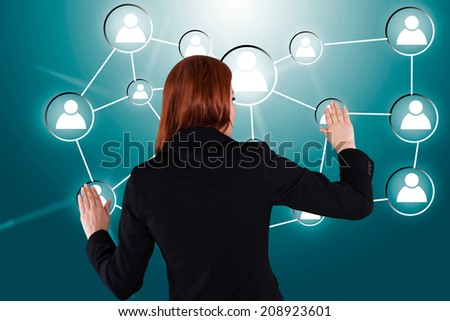 Rear view of businesswoman touching connected human icons over green background