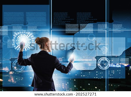 Rear view of businesswoman touching icon of digital screen - stock photo