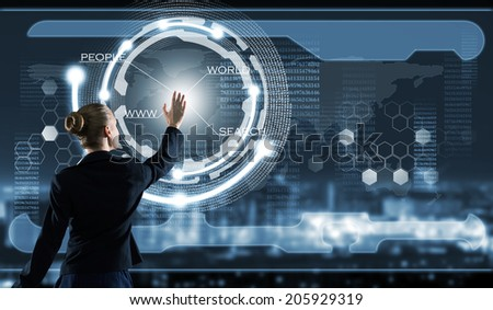 Rear view of businesswoman touching icon of media screen - stock photo