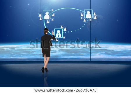 Rear view of busineswoman touching digital screen - stock photo
