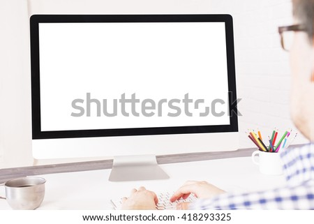 Rear view of caucasian businessperson typing on keyboard in front of a blank computer screen. Mock up - stock photo