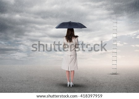 Rear view of classy businesswoman holding umbrella against desert landscape