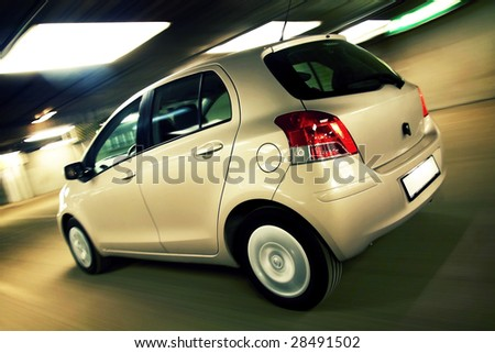 Rear view of compact hatchback driving fast in parking house - stock photo