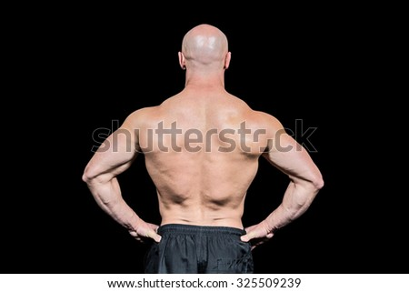 Rear view of confident bald man with hands on hip against black background - stock photo