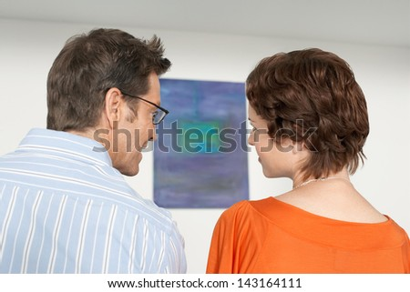 Rear view of couple discussing painting in art gallery - stock photo