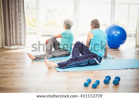 Rear view of couple doing yoga on exercise mat at home - stock photo