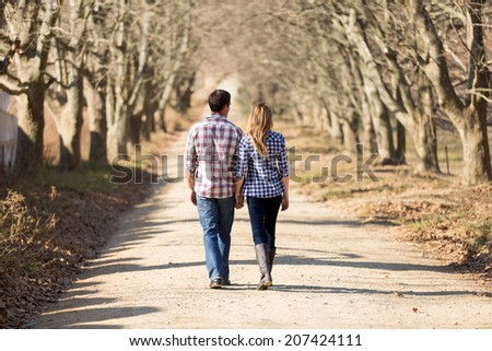 rear view of couple holding hands walking in autumn countryside - stock photo