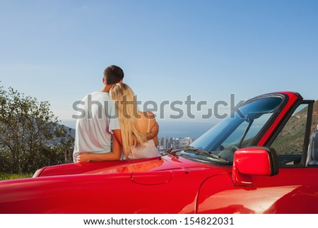 Rear view of couple hugging and admiring panorama on a sunny day - stock photo
