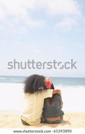 Rear view of couple hugging on beach - stock photo