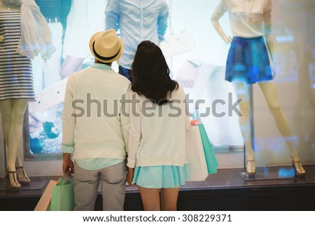 Rear view of couple looking at the clothes in the shop window - stock photo