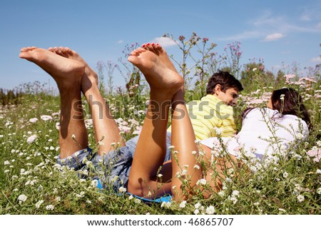 Rear view of couple lying on the grass and chatting - stock photo