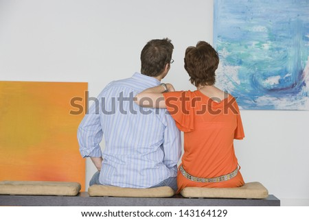 Rear view of couple observing painting while sitting on bench in art gallery - stock photo