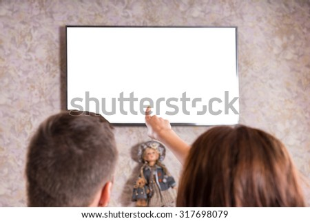Rear View of Couple on Sofa Watching Flat Screen Television Mounted on Living Room Wall, View of Back of Heads with Woman Pointing - Screen is Blank for Copy - stock photo