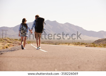 Rear View Of Couple On Vacation Hitchhiking Along Road - stock photo