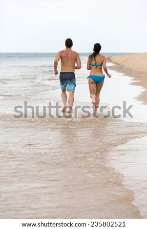 rear view of couple running on a tropical beach - stock photo
