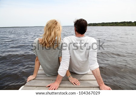 Rear view of couple sitting on a wooden bridge by a lake - stock photo